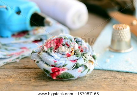 Floral linen brooch. Fabric flower brooch decorated with beads, hot glue gun, scissors, thread spool, thimble, felt sheet on vintage wooden table. Summer women brooch DIY concept. Closeup