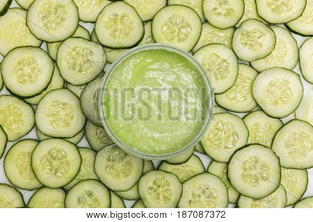 Top View Of Cucumber Face Cream In Container And Cucumber Slices