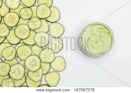 Top View Of Cucumber Face Cream In Container And Cucumber Slices Isolated On White