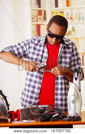 Young African Ecuadorian male Technician wearing protection glasses and using a metal cutter with office background.