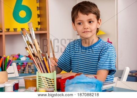 Small student boy painting in art school class. Child drawing by paints on table. Boy in a children's club. Craft drawing education develops creative abilities of children.