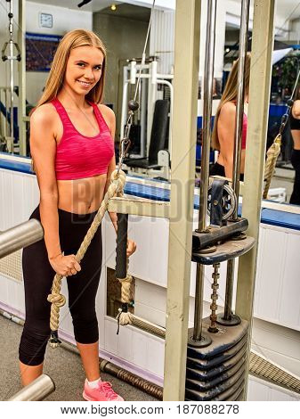 Woman in gym workout with fitness equipment. Girl working on bicep curl machine with rope in sport gym. Reflection female in mirror. Female makes her figure better with help of physical exercises.
