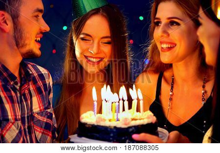 Happy friends birthday celebrating food with celebration cakes. Meet four people wear in hat party blow out burning candles. Group women and men have fun in nightclub. Meeting graduates and holiday.