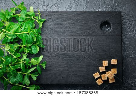 Fresh mint leaves on a black wooden board. Selective focus. Top view. Copy space.