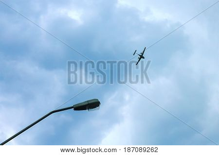 Plane fly above the land near the light pole