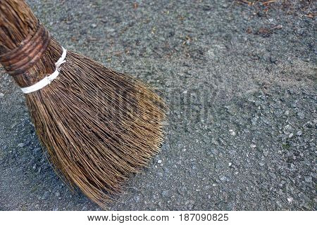 An old broom sweeps an asphalt street