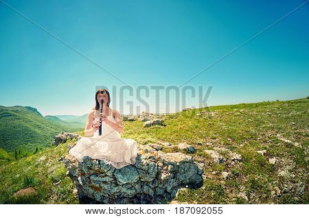 Young Woman In White Dress Playing On Vintage Flute On The  A Mountain Landscape