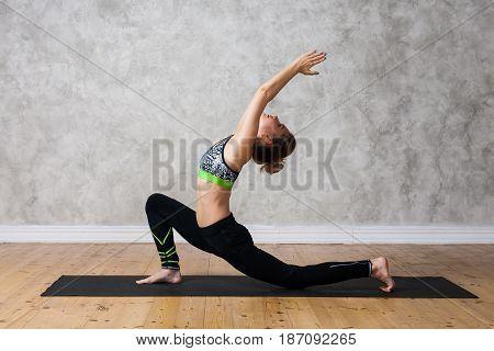 Young Woman Practicing Yoga Low Lunge Pose, Urdhva Ashva Sanchalasana  Against Texturized Wall / Urb