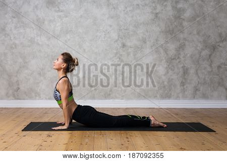 Young Woman Practicing Upward Facing Dog, Urdhva Mukha Svanasana Yoga Pose Against Texturized Wall /