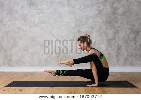 Young Woman Practicing Yoga Challenge Pose, Eka Hasta Bhujasana Against Texturized Wall / Urban Back