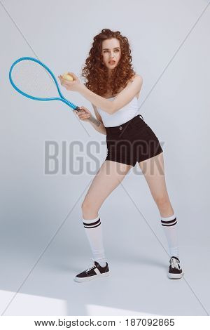 Full Length View Of Beautiful Young Hipster Girl Playing Tennis With Racket And Ball