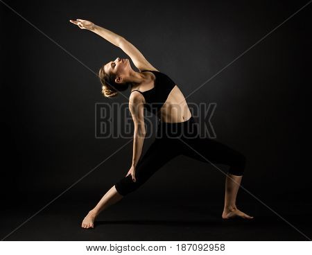 Sporty Beautiful Young Female Doing Yoga Warrior Pose Right / Virabhadrasana  On Dark Black Backgrou