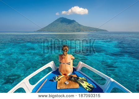 Young woman in swimsuit sit on boat with a mask and flippers looking to a clean sea and volcano Manado Tua. North Sulawesi Indonesia.