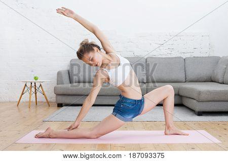 Young Beautiful Woman Doing Warrior Pose / Virabhadrasana On Pink Mat At Home .
