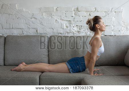 Young Beautiful Woman Doing Upward Facing Dog / Urdhva Mukha Svanasana On Sofa At Home