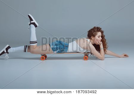 Side View Of Young Hipster Woman Lying On Skateboard Isolated On Grey