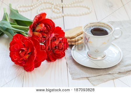 Morning coffee and a bouquet of tulips on a wooden table.