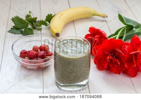 Smoothies in a glass and a bouquet of tulips on a wooden table.