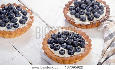Sweet Blueberry Tarts On A White Wooden Board