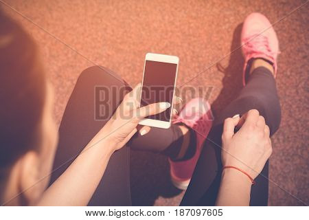 Female jogger sitting on bench next to the jogging track and using smartphone with blank screen. Preparing for the morning workout. Top down point of view. Technology sport and fitness concepts.