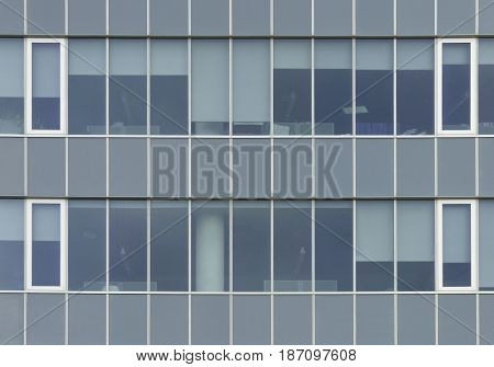 Office building glass wall with windows - industrial wallpaper. Horizontal and vertical stripes, regular structure.