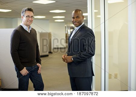 Smiling businessmen standing together in office