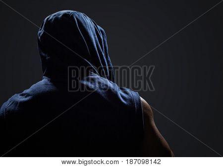 Back of man with hoodie against dark grey background