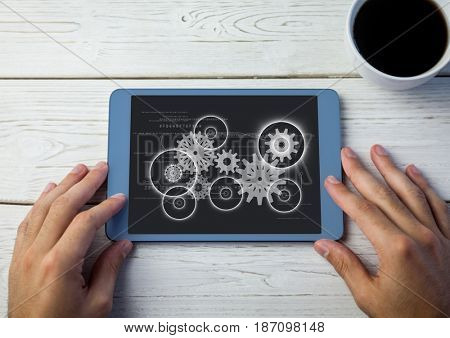Digital composite of Overhead of hands with tablet and tea and white cog graphics