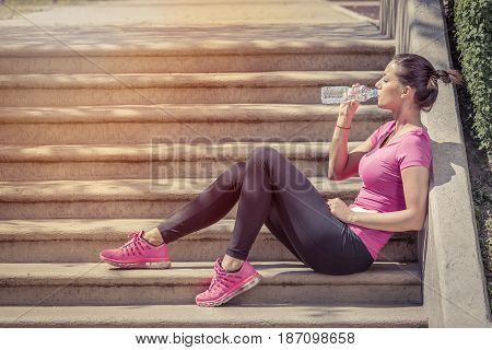 Fitness runner woman drinking water and sitting on staircase. Athlete girl taking a break during run to hydrate during hot summer day. Healthy active lifestyle.