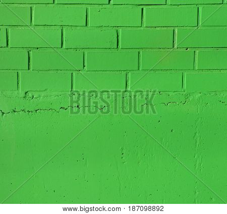 Bright green brick wall and a plaster texture. Closeup view of solid surface with regular structure. Industrial or construction background with place for text