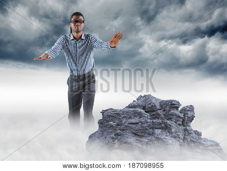 Digital composite of Business man blindfolded on misty mountain peak against storm clouds