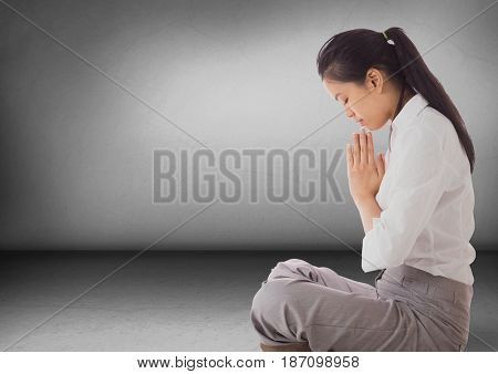 Digital composite of Business woman with praying in grey room
