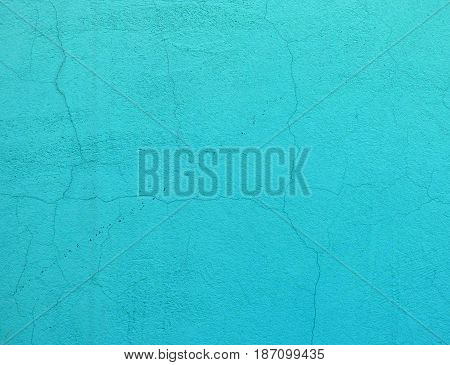 Cyan plaster texture with lot of small cracks. Closeup view of solid surface with random structure. Light blue industrial background with place for text.