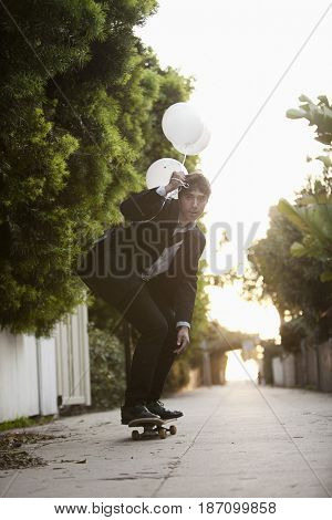 Caucasian businessman holding balloons and riding on skateboard