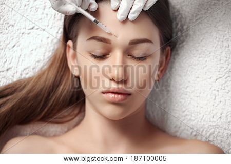 Portrait of woman getting cosmetic injection. Clean Beauty. Closed eyes.