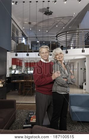 Smiling Caucasian couple standing together in living room