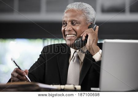 Black businessman talking on telephone at desk