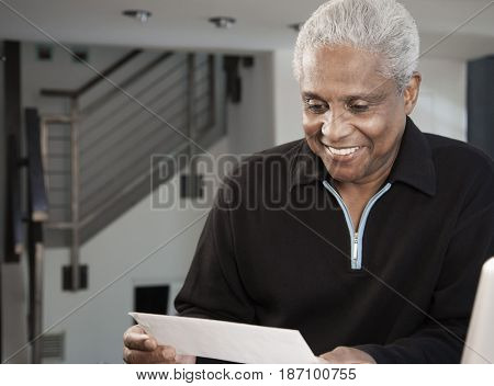 Smiling black man looking at paperwork