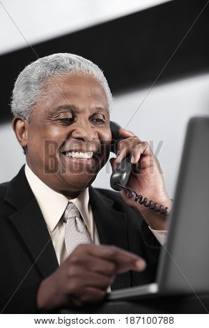 Black businessman talking on telephone and using laptop