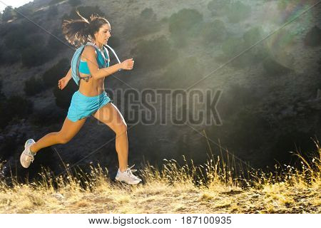 Hispanic woman running in remote area