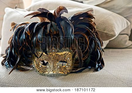 Venetian mask with feathers on cloth near pillows