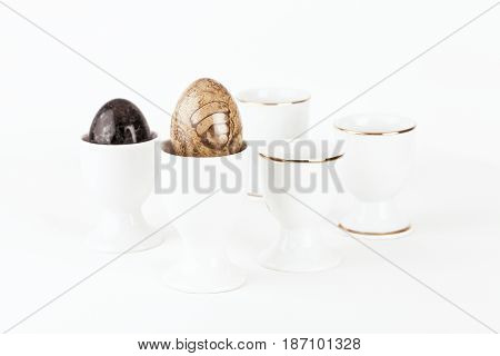White eggcups, eggs of stones in close up. Colorful eggs of processed stone in the cups, white background.