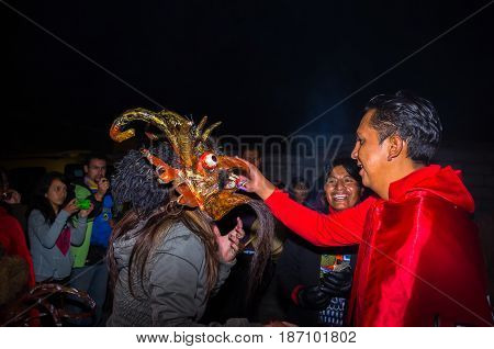 Quito, Ecuador - May 27, 2015: An unidentified people wearing a red jacket while the woman is using a devil mask in the diablada.