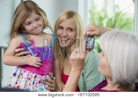 Smiling Caucasian grandmother, mother and daughter taking pictures