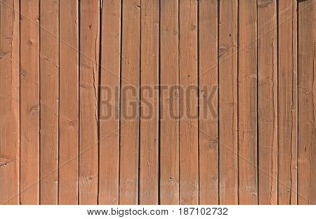 Brown wooden plank texture with some knots and scratches. Retro background - aged lumber surface.