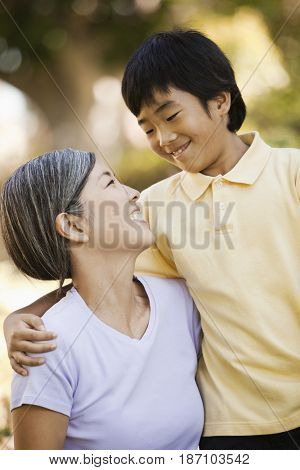 Smiling Asian mother and son hugging