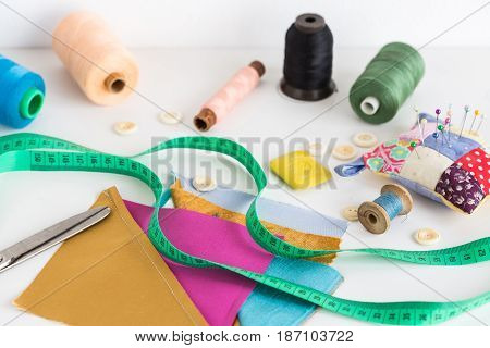 sewing tools, patchwork, tailoring and fashion concept - closeup on white desk with measuring meter, thread spools, pincushion, buttons, scissors, pieces of colored patchwork fabric, soap