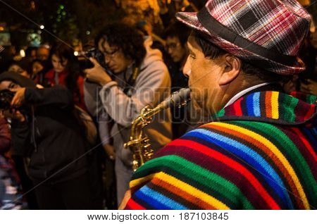Quito, Ecuador - february 02, 2016: An unidentified man playing his instrument during popular town celebrations.