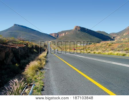 WORCESTER, WESTERN CAPE, SOUTH AFRICA, ROAD IN FORE GROUND, LEADING INTO THE MOUNTAINS IN THE BACK GROUND 22likj