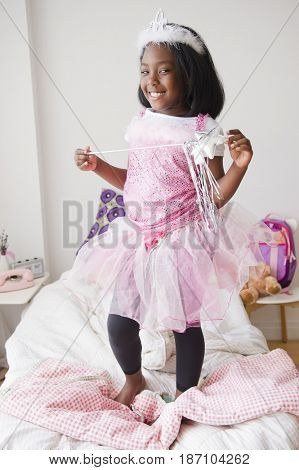 Black girl in fairy costume standing on bed